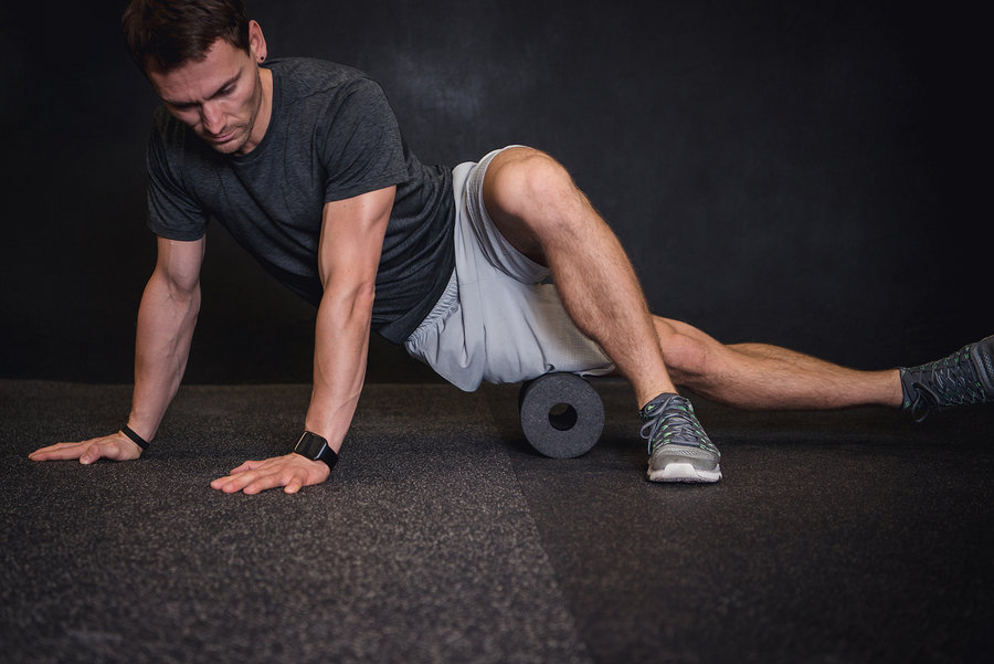 Athletic man using a foam roller to relieve sore muscles after a workout.