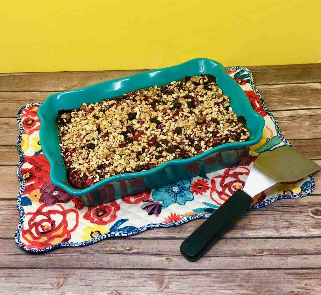 Granola berry crisp on a flowered placemat with a serving spatula