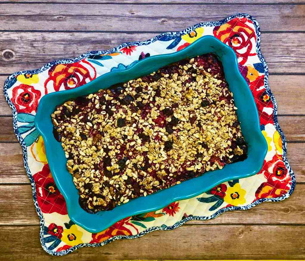 Berry Crisp in a casserole dish on a flowered placemat with a wood background.