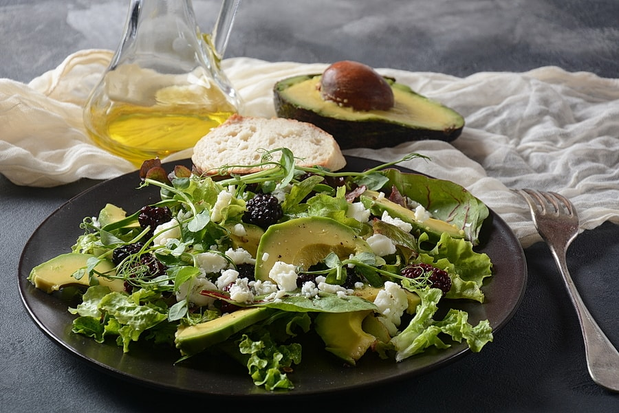 Avocado salad with lettuce, blackberry, blue cheese, olive oil and arugula on a plate. Healthy vegan food concept