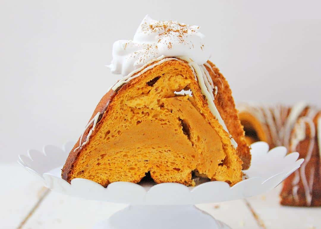 Pumpkin angel food cake with whipped cream on a white background