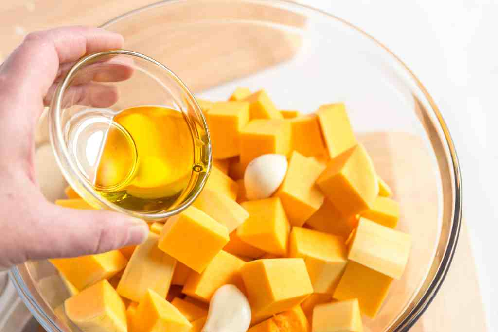 Butternut squash cut into chunks and garlic cloves in a glass bowl with olive oil being drizzled on top.
