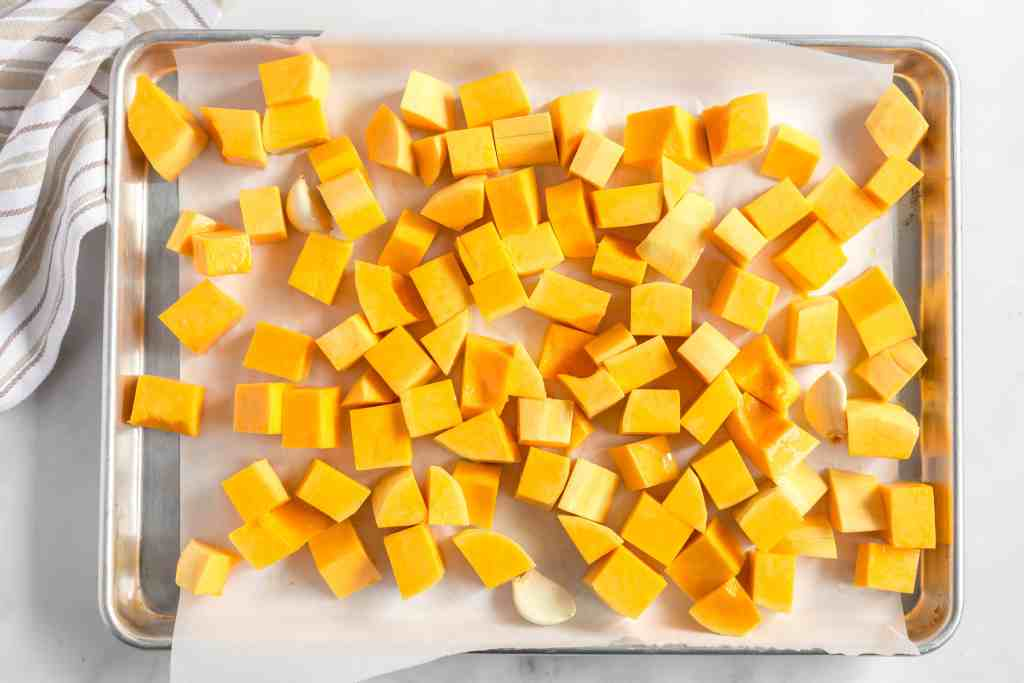 Butternut squash and garlic cloves on a baking pan.