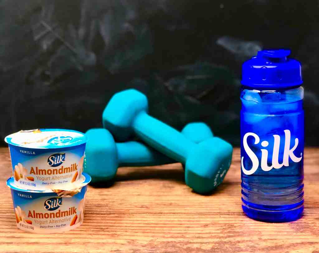 Silk almond yogurt, ice water in Silk bottle and weights on wood background.
