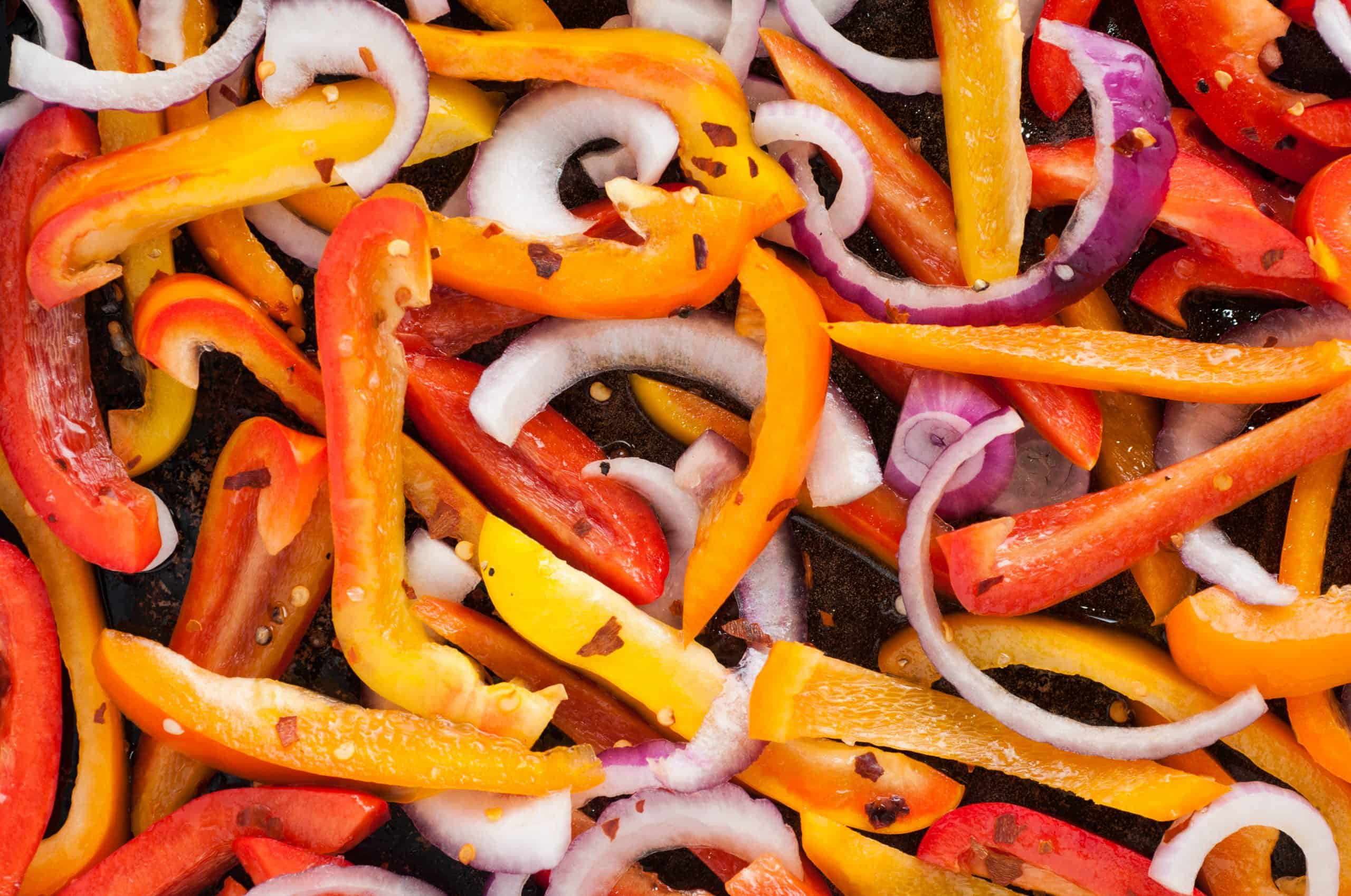 Close up of bell pepper strips and onion with crushed red pepper and olive oil.