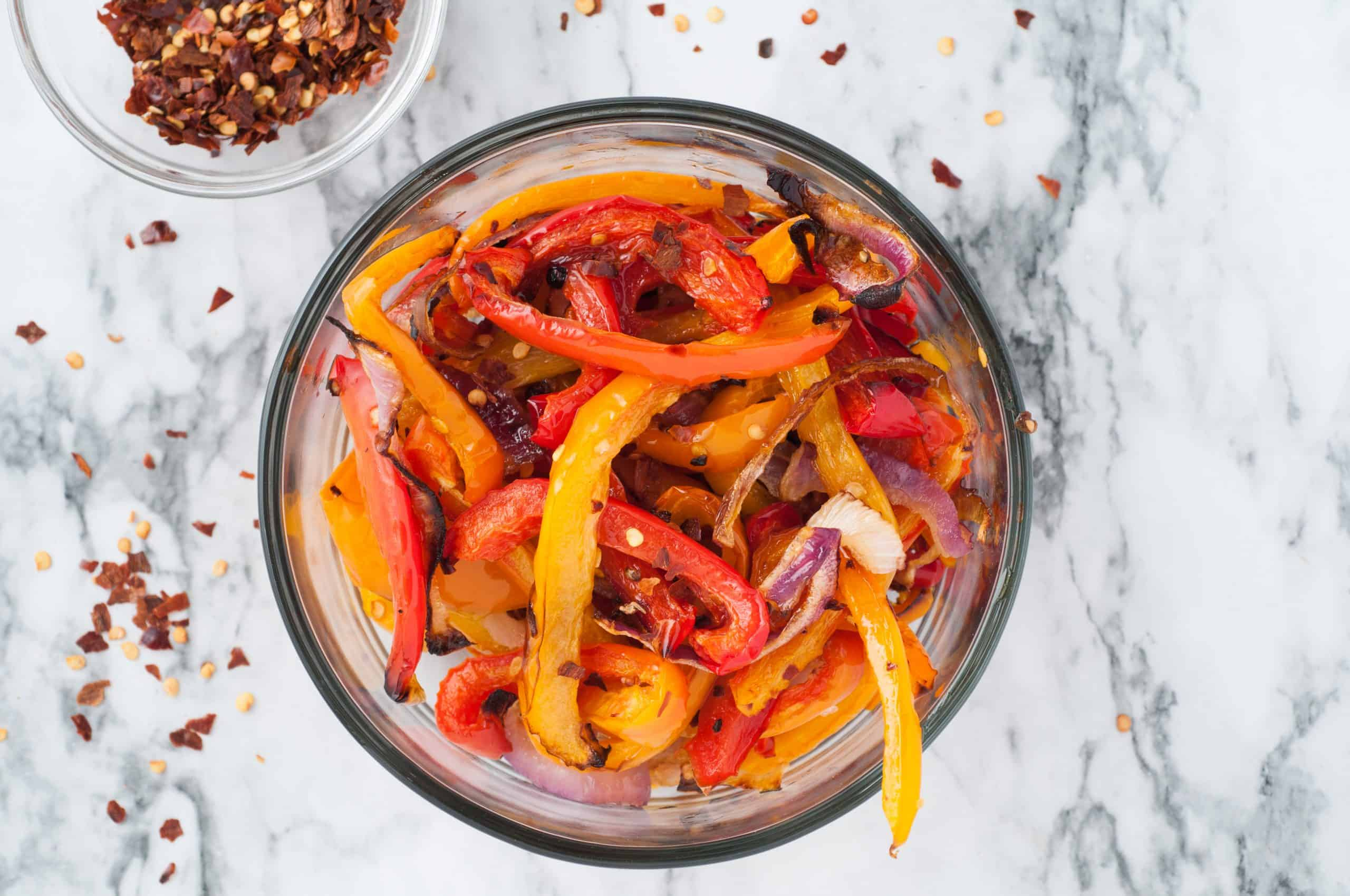 Bell Pepper Strips and Onions in a glass bowl on a white marble background with crushed red pepper in a bowl and sprinkled around it.