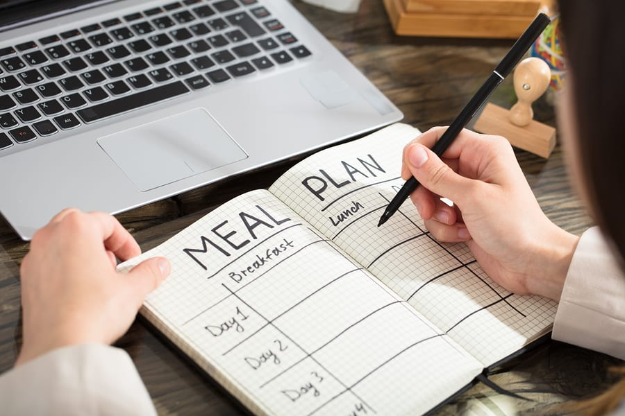 Businesswoman Writing Down A Meal Plan In Checkered Notebook With Black Marker Over The Desk