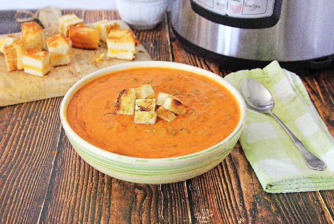 Tomato soup with grilled cheese croutons on wood background with Instant Pot in background.