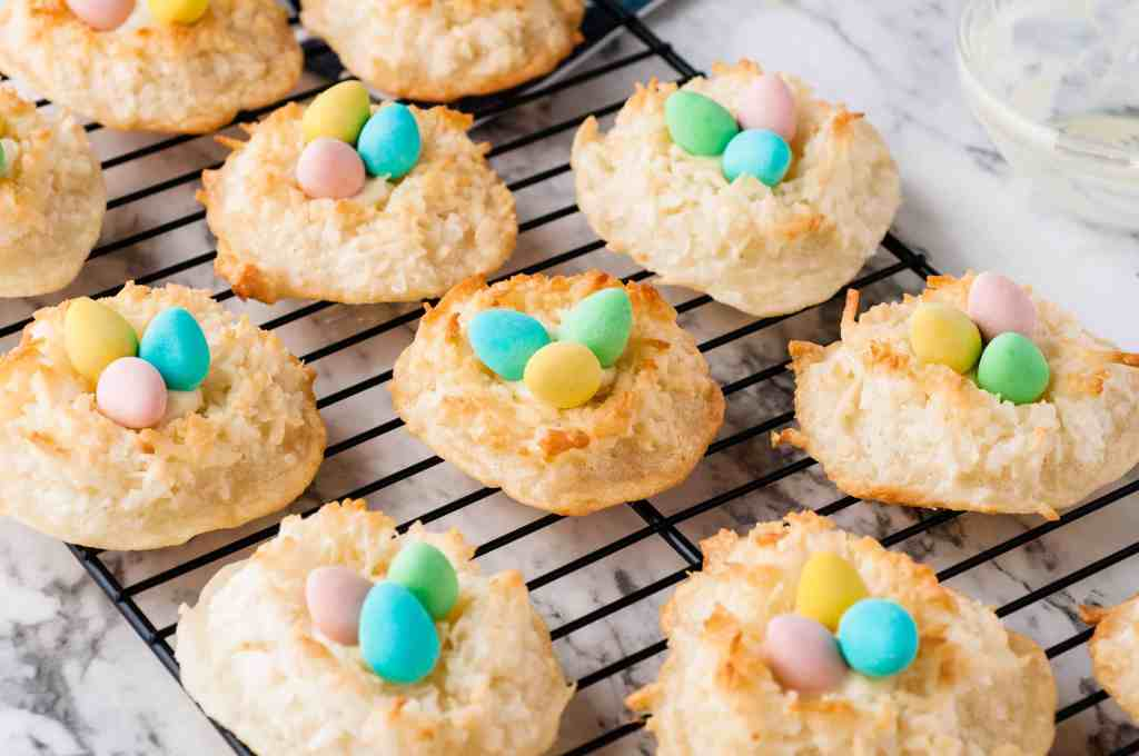 Bird's nest cookies with mini Cadbury eggs in the center on a wire rack.