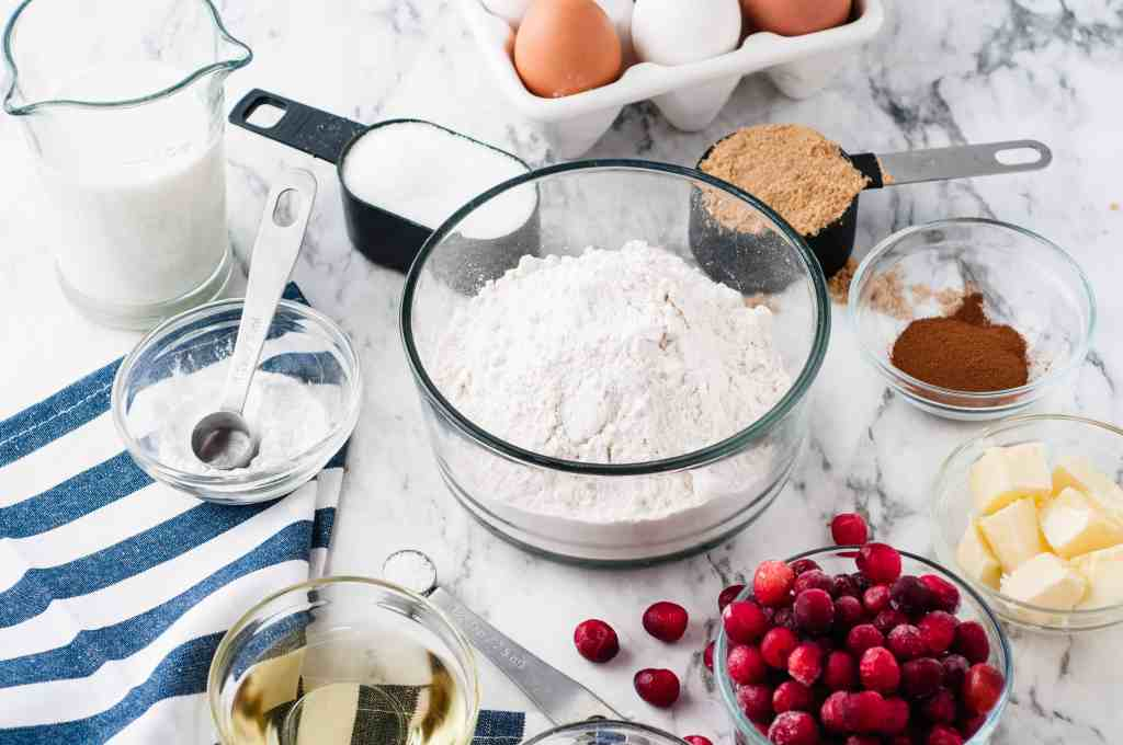 Flour, cranberries, oil, milk, butter, eggs and cinnamon on a white background with a blue and white striped towel.