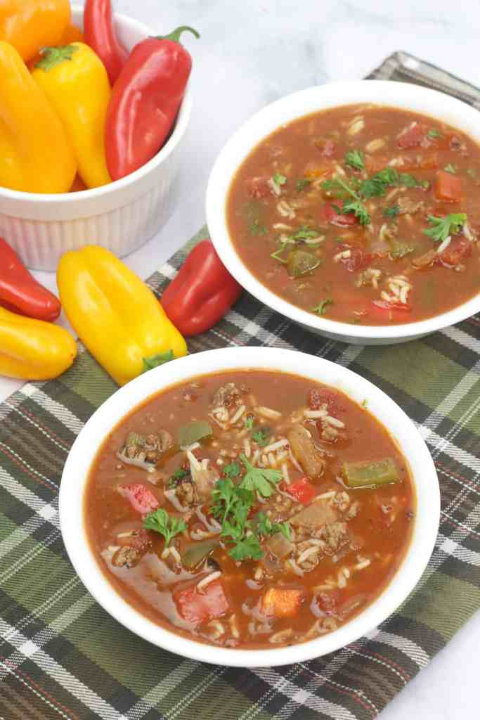 2 bowls of soup with red and yellow peppers beside it.