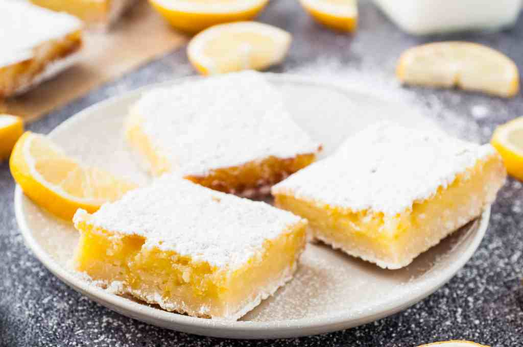 Lemon shortbread squares served on a white plate with fresh slice of lemon.