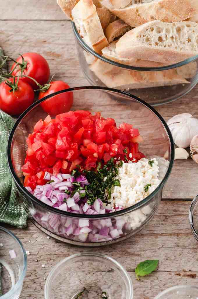Tomato, feta, red onion and herbs in a glass bowl.