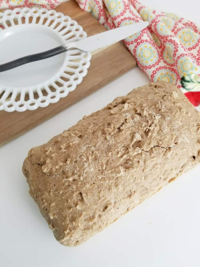 fresh baked wheat bread on a white cutting board