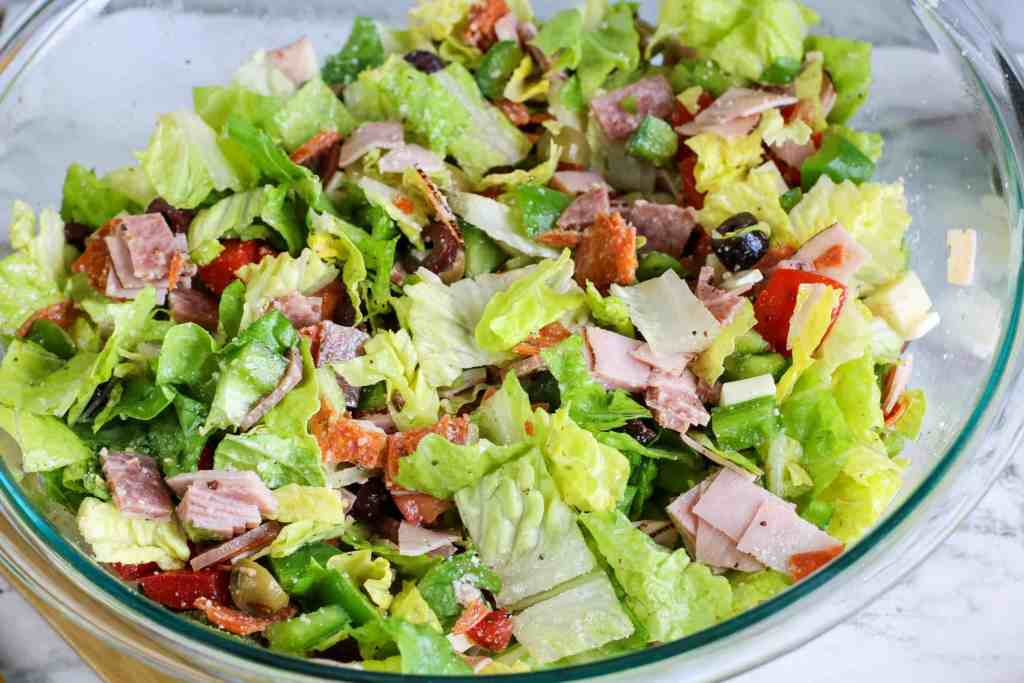 Italian salad in a large glass bowl on a white marble background.