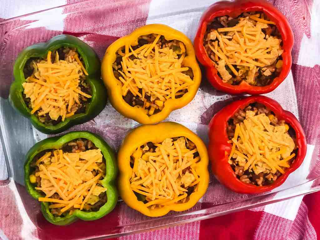Overhead shot of stuffed stoplight peppers with cheese on top.