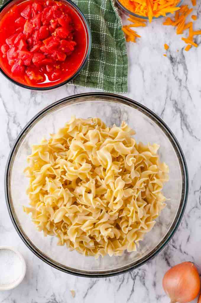 Egg noodles for cheesy beef and noodle casserole in a large glass bowl