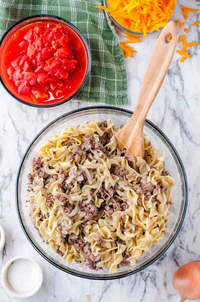 Beef and egg noodles combined in a large glass bowl for casserole with a bowl of canned diced tomatoes to side.