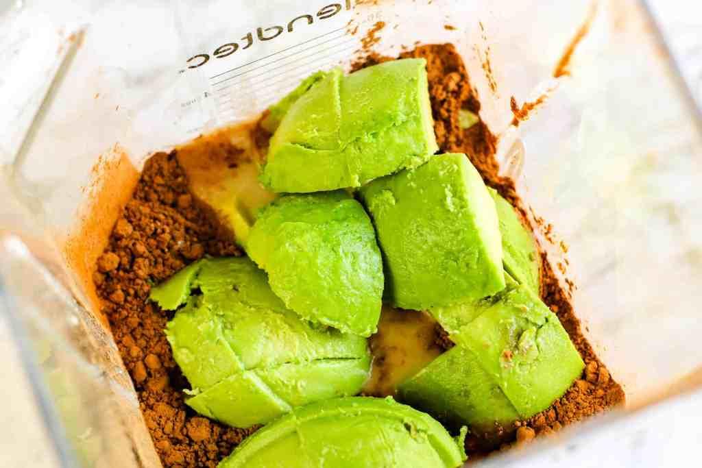 Avocado in blender on top of cocoa and coconut milk.