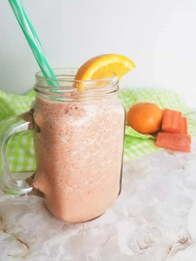 Carrot Orange Smoothie in a glass mug with an orange slice and a green striped straw.