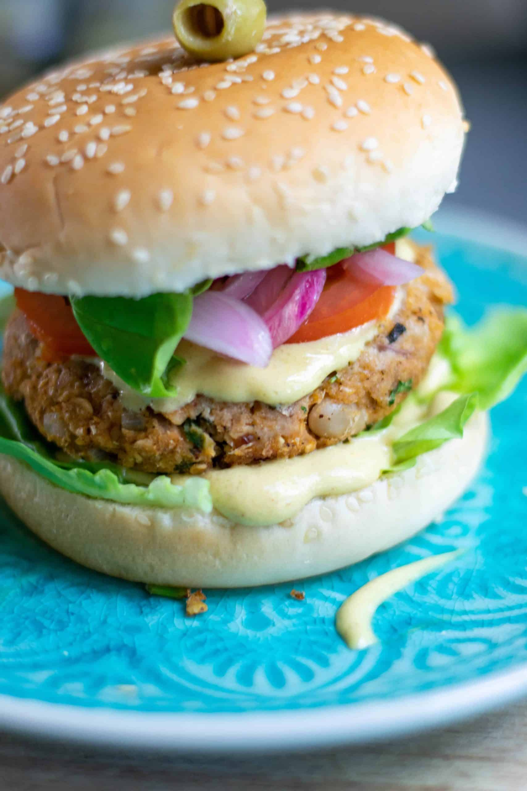 Angled photo of white bean burger on a blue plate.