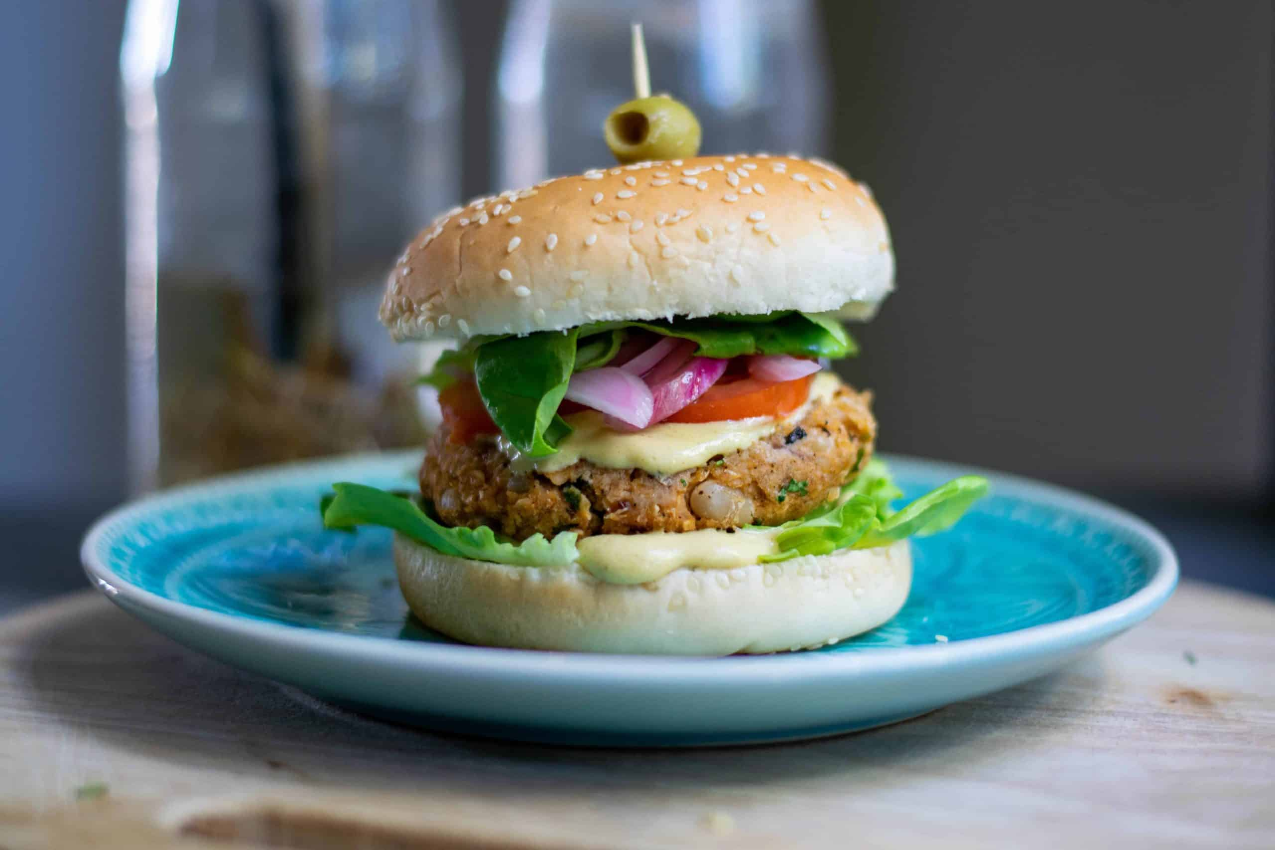 Vegan white bean burger on a Lue plate with an olive on top.