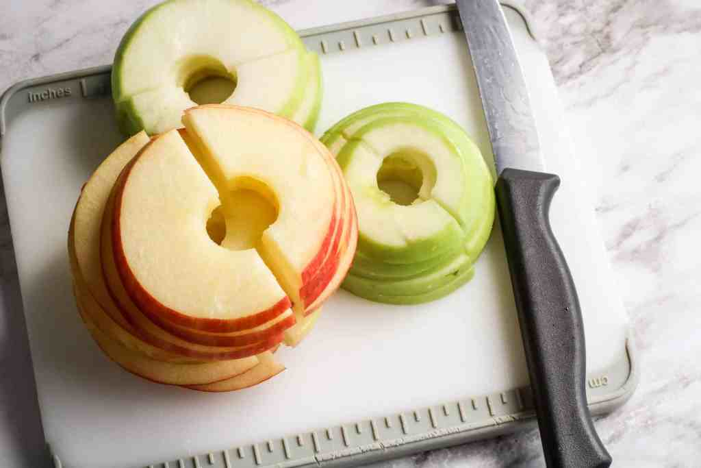 Sliced Macintosh and Granny Smith Apples on a cutting board with a knife on the right side.