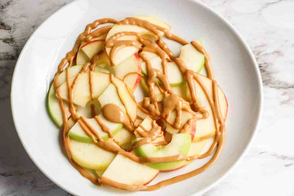 Apple slices on a white plate drizzled with peanut butter.