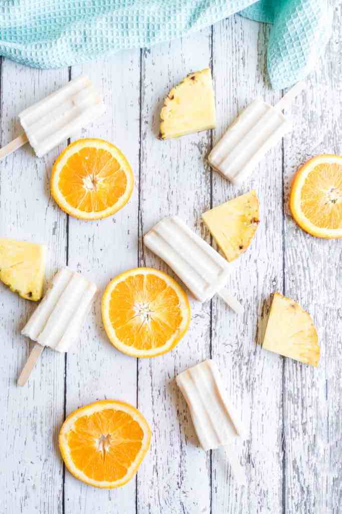 Popsicles on a white board with orange slices and pineapple chunks.