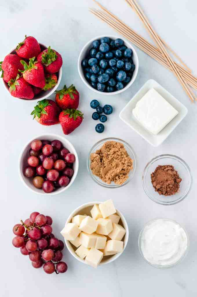 Overhead shot of strawberries, blueberries, grapes, brown sugar, cheese cubes, cream cheese, sour cream, Cocoa and skewers