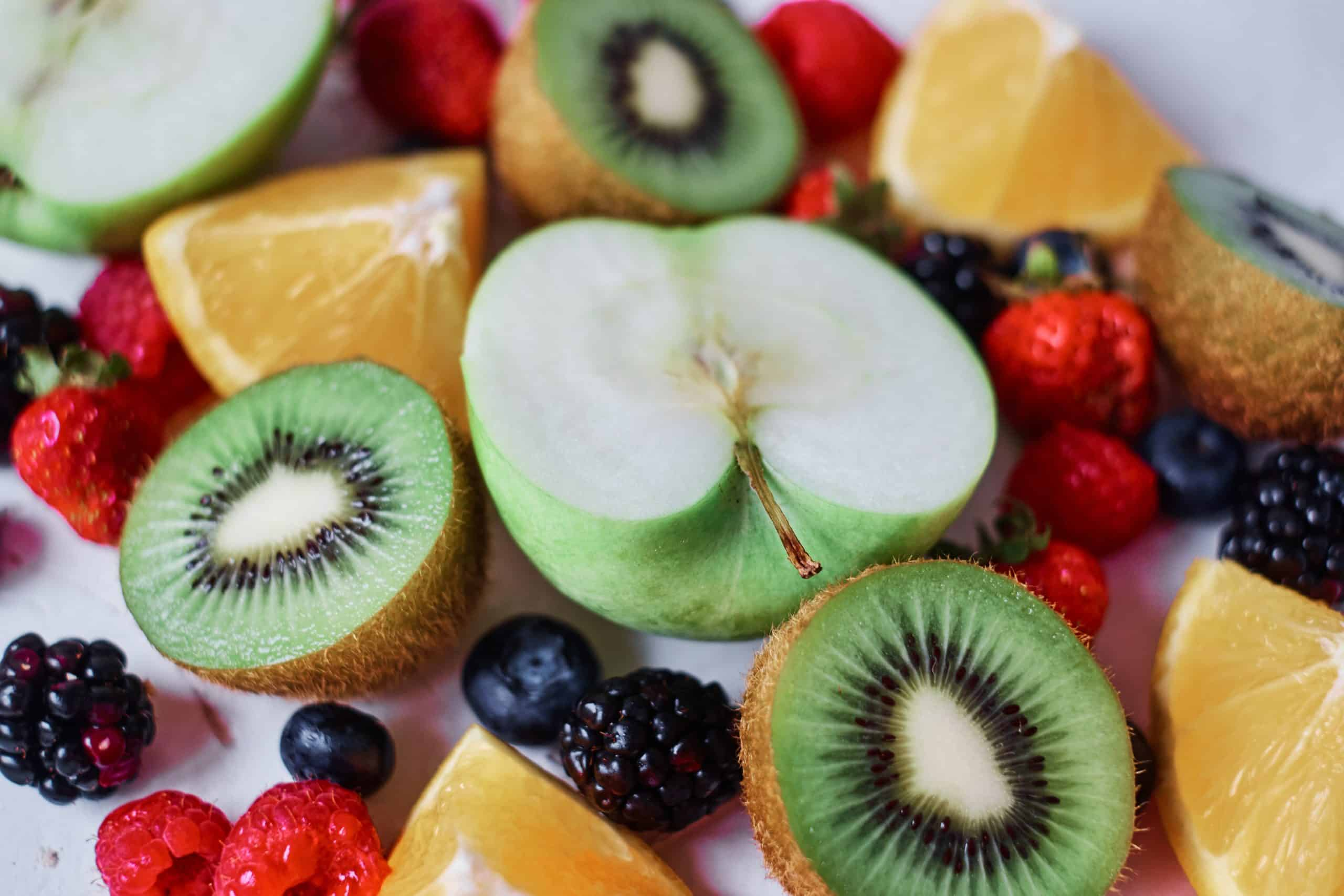 Kiwis and green apples sliced in half, with quartered oranges, blackberries, blueberries and raspberries on a white background.