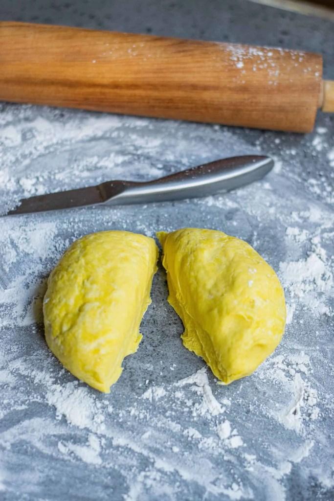 Homemade Pumpkin Pasta Dough cut in half on a floured surface.