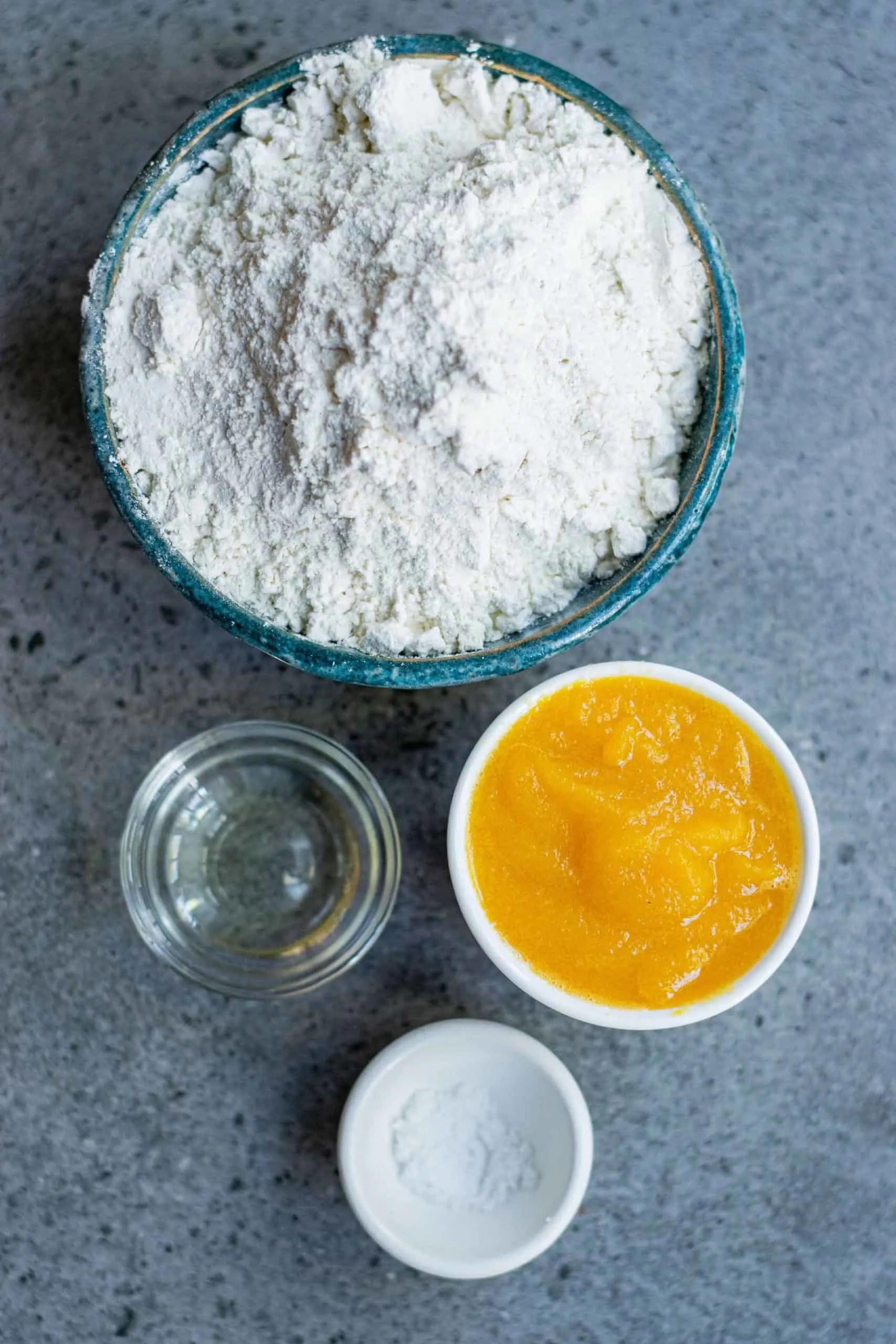 Flour, Pumpkin Purée, Sunflower Oil and salt on a marble counter top.