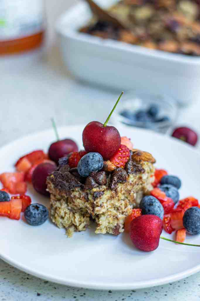 Vegan Baked Oatmeal with fresh fruit on a white plate.