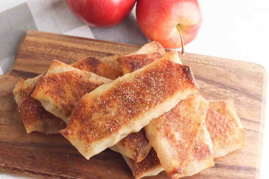 Apple Pie Egg Rolls on a wooden cutting board.
