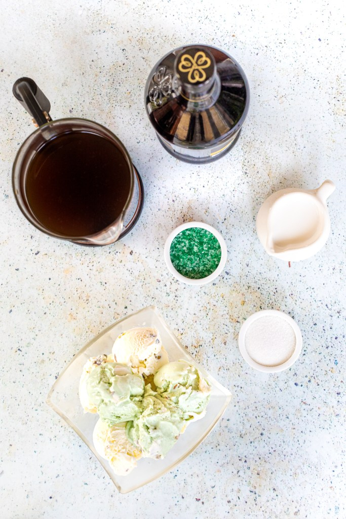 Overhead view of cold brew coffee, green sprinkles, pistachio ice cream, sugar and sweet cream
