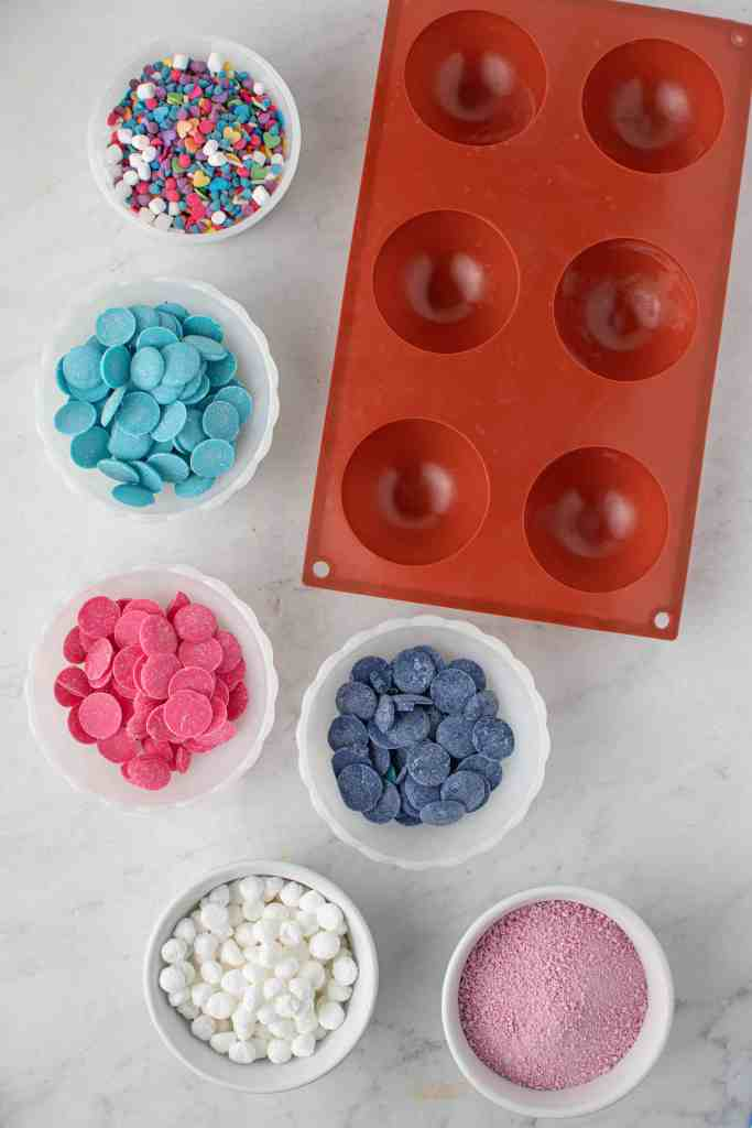 Ingredients for Galaxy Hot Cocoa Bombs beside silicone half sphere mold.
