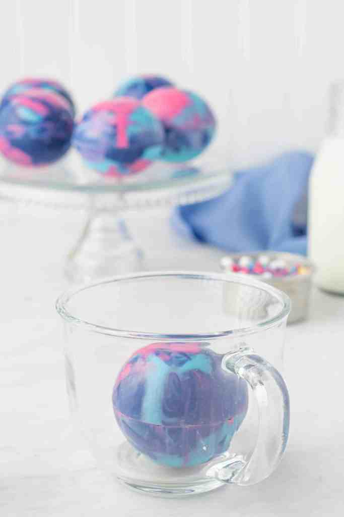Galaxy hot cocoa bomb in glass cup with 4 bombs in background ion a glass cake stand.