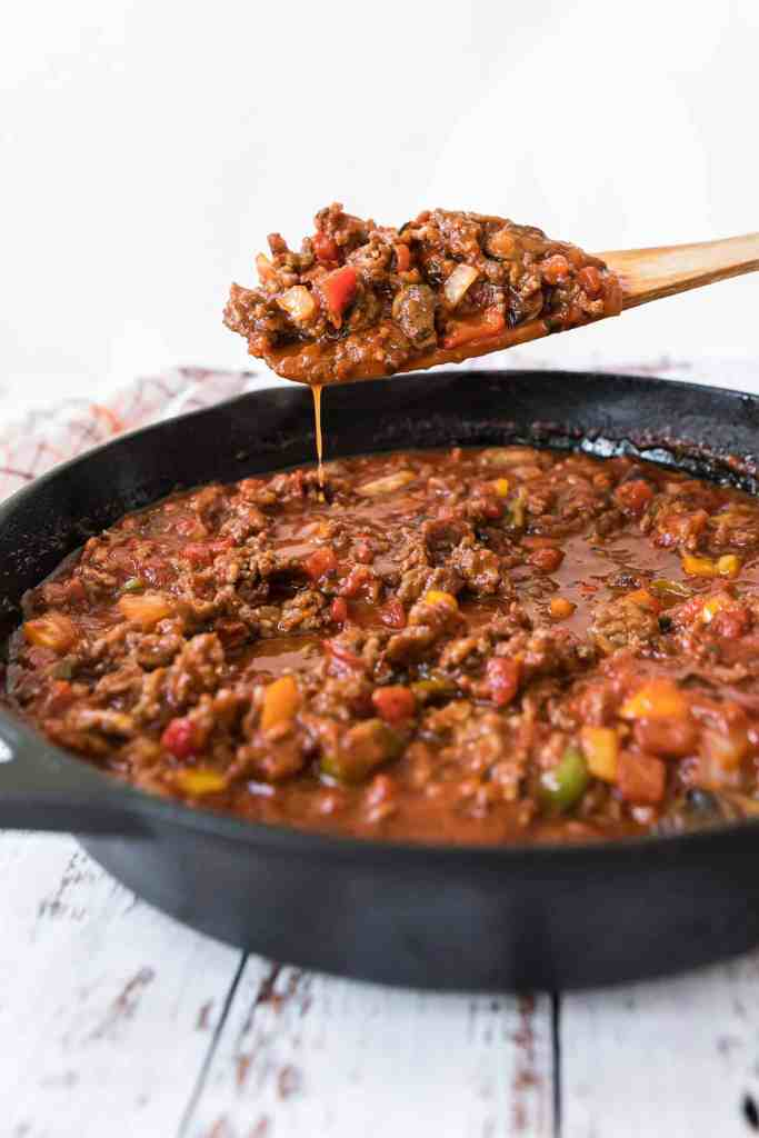 Homemade meat sauce in a black iron skillet with a wooden spoon of it over the skillet.