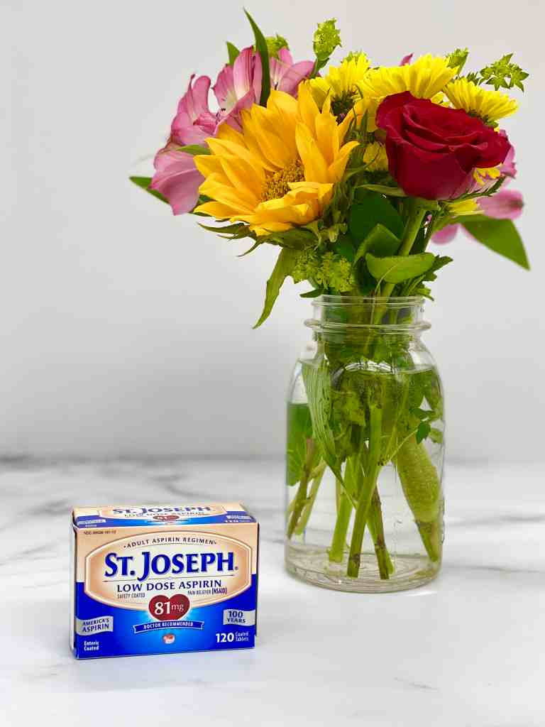 St. Joseph's aspirin on a marble countertop with a vase of spring flowers in the background.