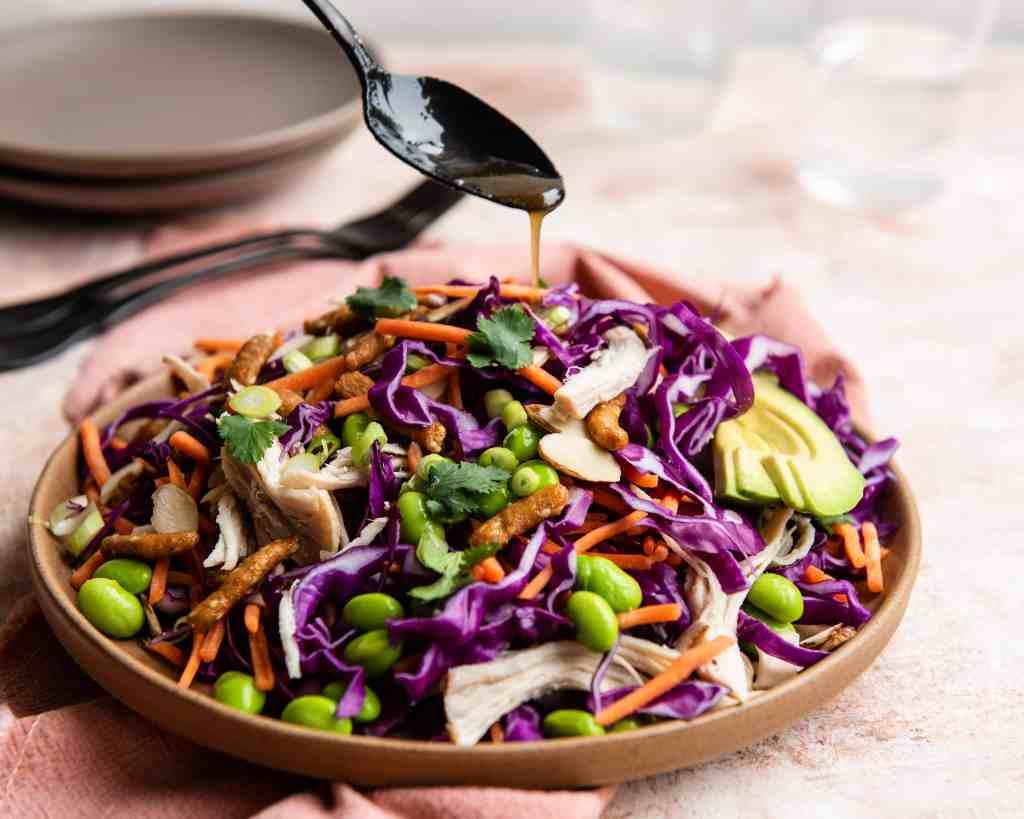 Asian Salad with Sesame dressing being spooned onto it.