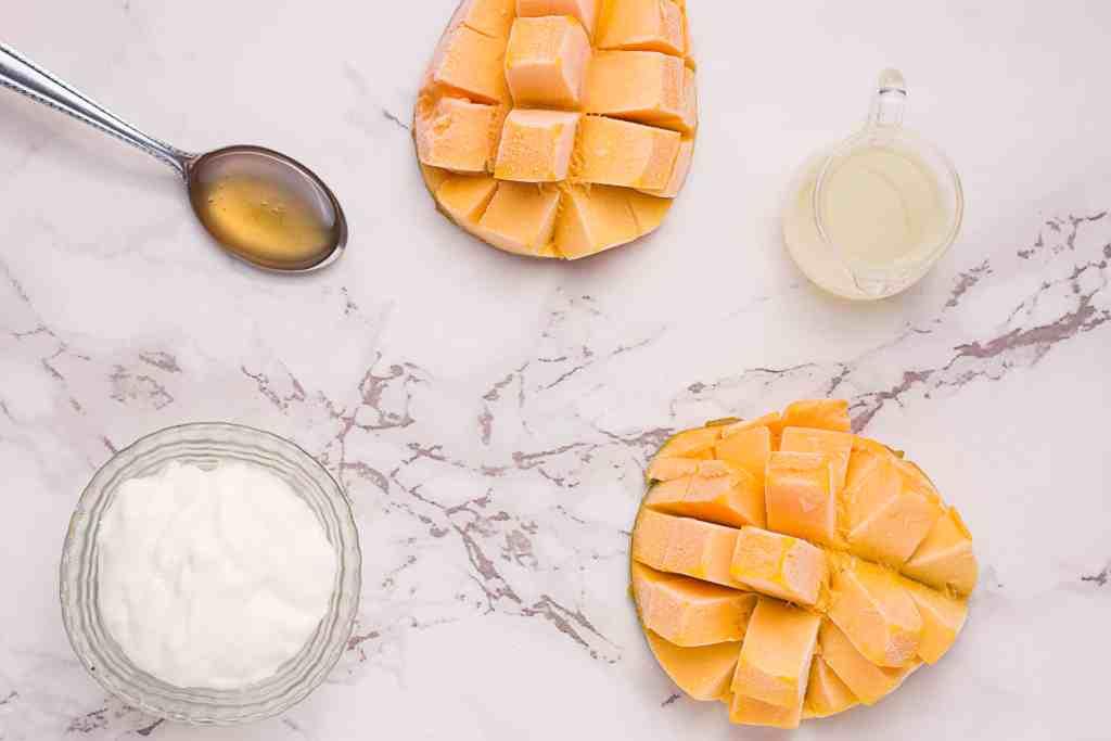 Mango, honey, lemon juice and yogurt on a marble counter top.