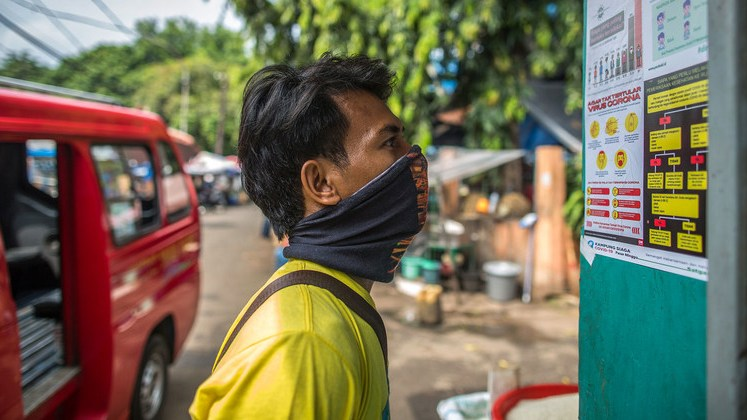 A man reads COVID-19 prevention information in Jakarta, Indonesia.