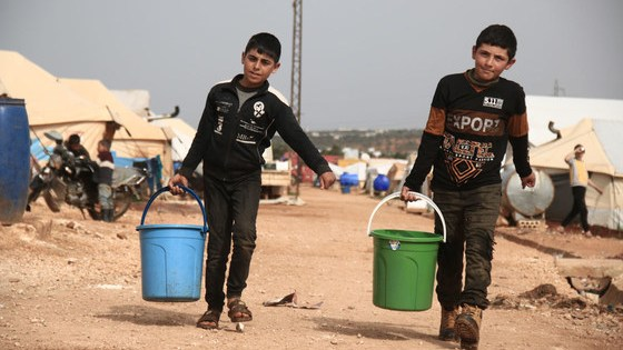 Two children collect drinking water in a camp for displaced people in Idlib, Syria.