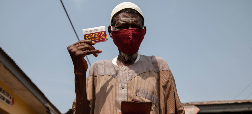 A 76-year-old man shows his vaccination card after receiving a COVID-19 vaccine in Kasoa, Ghana.