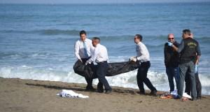 Personal de los servicios funerarios procediendo a trasladar uno de los cadáveres en la tarde de este lunes en la playa de La Venus