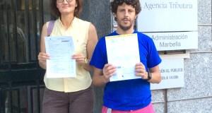 Los concejales de Costa del Sol Sí Puede, Victoria Mendiola y José Carlos Núñez, muestran sus declaraciones de renta ante la sede de Hacienda este miércoles.