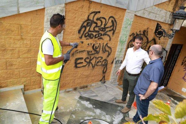 Imagen de los trabajos de retirada de pintadas con el edil de Limpieza, Diego López, al fondo. FOTO/ Ayto de Marbella