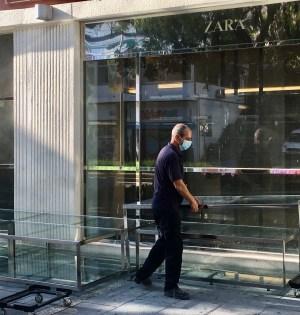 Un operario de Zara traslada estanterías y mobiliario interno a las puertas del establecimiento en Ricardo Soriano. FOTO/ CABANILLAS