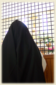 Photo of a Dominican Nun praying by the enclosure grille